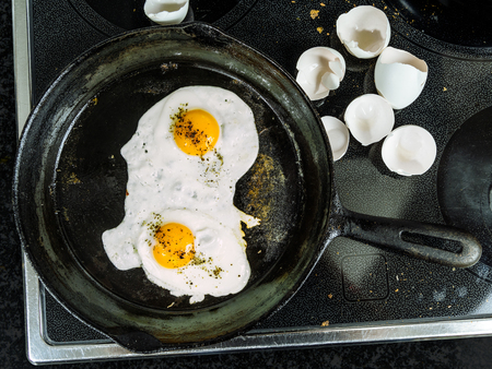 stovetop: Photo of two eggs frying in a cast iron skillet on top of a stove with egg shells to the side.