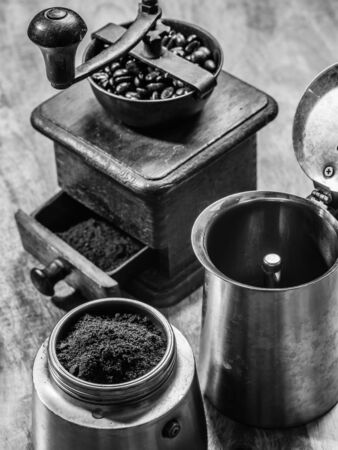 espresso: Photo of an Italian Moka Express stovetop coffee maker and a coffee grinder done in black and white.