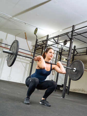 jerk: Photo of a young woman doing a clean and jerk bodybuilding exercise at the gym. Stock Photo