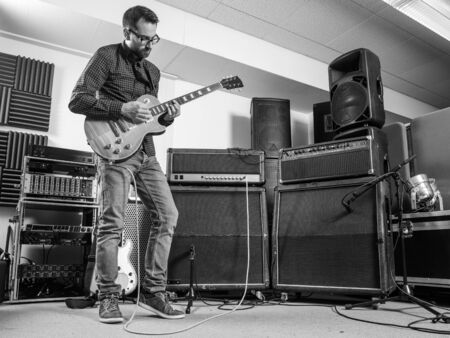 Photo of a man in his late 20s standing in a recording studio playing his electric guitar.