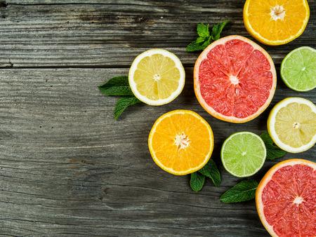 CITRICOS: Foto de pomelo una rebanada, naranja, limón y lima en una antigua losa rústica de la tarjeta del granero. Foto de archivo