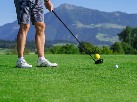 Photo of a male golfer teeing off on a golf course on a beautiful day. Stock Photo
