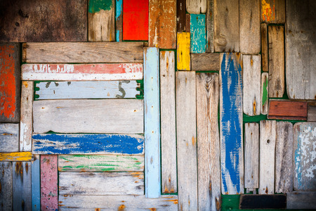 Photo of a well worn wooden wall with multicoloured planks and vignetting added. Standard-Bild