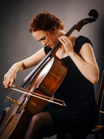 adult entertainment: Photo of a beautiful woman concentrating on her cello playing. Stock Photo