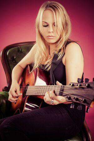 ragazze bionde: Foto di una bella donna bionda suonare una chitarra acustica. Archivio Fotografico