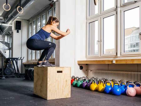 Photo of a young woman doing a box jump at the gym.