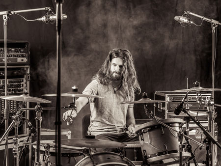 Foto van een jonge mannelijke drummer met lang haar spelen zijn drum set.