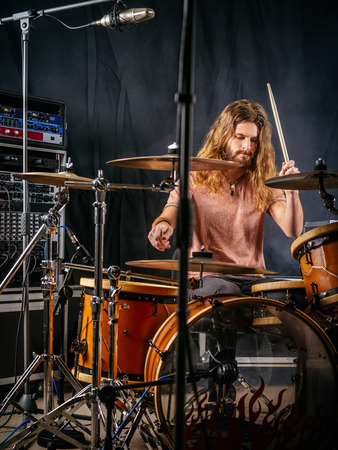 adult entertainment: Photo of a male drummer playing his drum set at a recording studio.