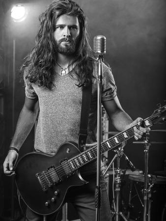Foto de un hombre joven con el pelo largo y la barba que toca la guitarra eléctrica en el escenario.
