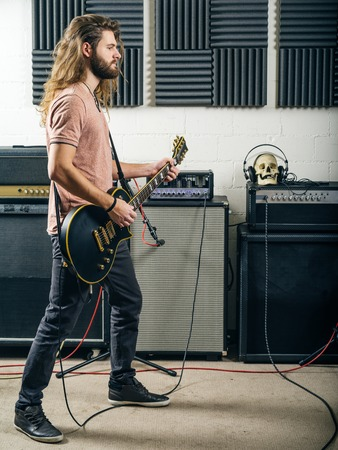 amp: Photo of an attractive man playing electric guitar in a recording studio.