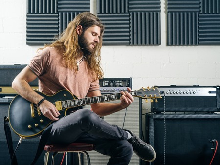 Photo of an attractive man playing electric guitar in a recording studio.