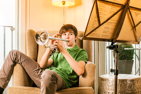 Photo of a teenage male practicing his trumpet at home. Stock Photo
