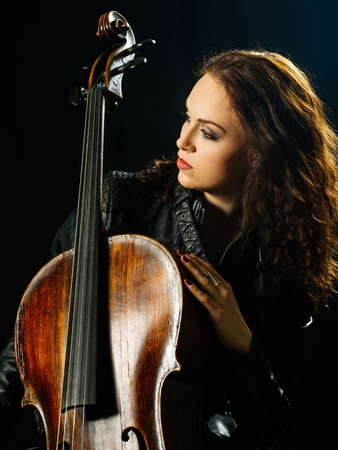 cellos: Photo of a beautiful woman posing with her old cello. Stock Photo