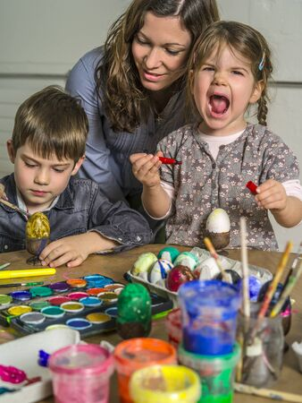 Photo of a mother and her children painting and decorating hard-boiled eggs for easter. photo