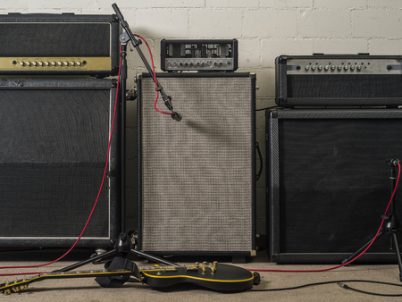 마이크와 일렉트릭 기타와 함께 녹음 스튜디오 설정에서 세 가지 기타 앰프의 사진.