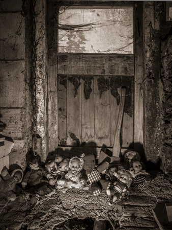 Photo of old dolls and an axe resting against an old barn door covered in spiderwebs and dust.
