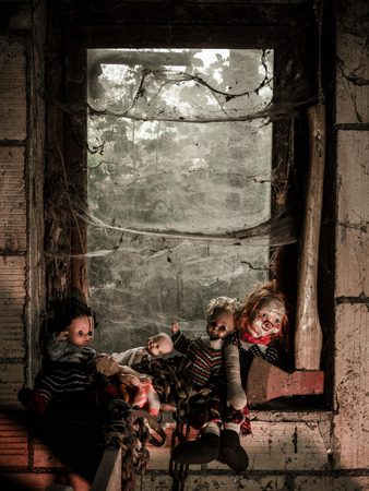 puppets: Photo of old dolls and an axe resting on an old window ledge covered in spiderwebs and dust.