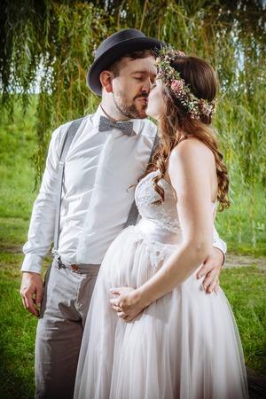 妊娠中に結婚式キス新郎新婦の写真。 写真素材