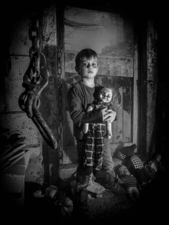 puppets: Photo of a creepy young boy holding an old clown doll in an old barn covered in spiderwebs and dust.