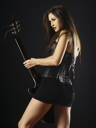 Photo of a beautiful young woman playing an electric guitar over black background. Archivio Fotografico