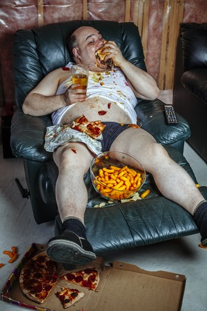 Photo of a fat couch potato eating a huge hamburger and watching television.  Harsh lighting from the television illuminates the dark room. Foto de archivo