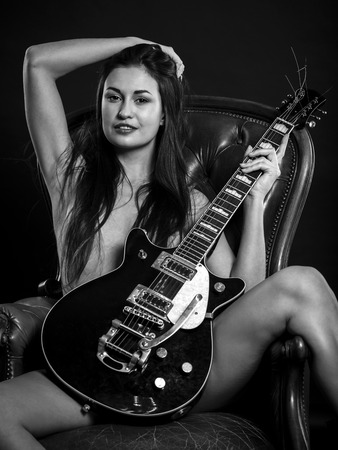 Photo of a beautiful young nude woman sitting on leather chair posing with an electric guitar.