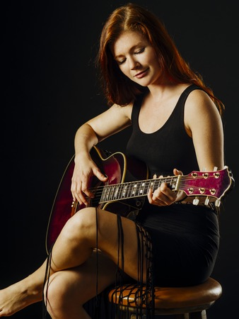 Photo of a young beautiful redhead woman sitting playing an acoustic guitar.