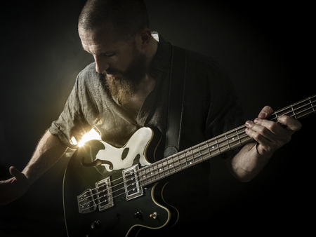 Photo of a bearded man playing bass guitar on stage in front of a spotlight.