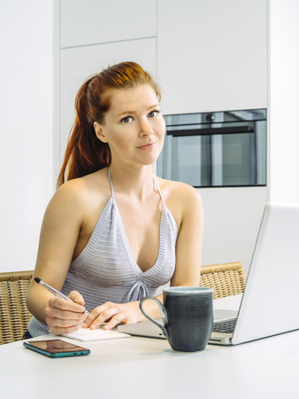 Photo of a gorgeous young redhead woman sitting in the kitchen working on her laptop and writing notes. Foto de archivo