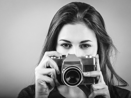 Photo of a beautiful woman pointing a vintage camera done in black and white. Banco de Imagens