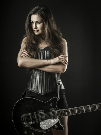 Photo of a beautiful young sexy woman holding an electric guitar over black background. Foto de archivo