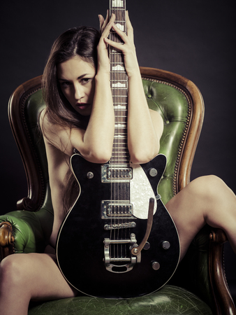 Photo of a beautiful young woman sitting on a leather chair and posing with electric guitar.