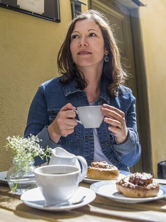 Photo of a woman sitting at an outdoor cafe in Gamla Stan, Stockholm, Sweden eating Kanelbulle and drinking coffee.