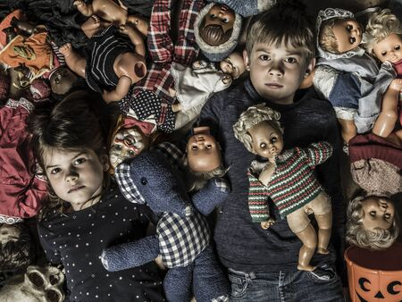 Photo of creepy young children on the floor surrounded by old dolls for Halloween theme.
