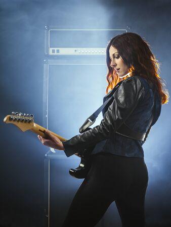 Young beautiful redhead woman playing an electric guitar in front of large amplifier. Foto de archivo