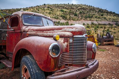 Large rusty old pickup truck rotting out in a field.