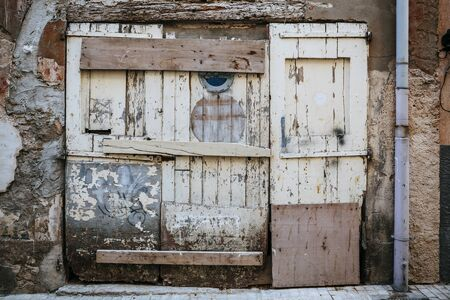 An old broken exterior door with rotting wood and peeling paint. Stock Photo
