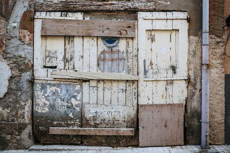 An old broken exterior door with rotting wood and peeling paint. 免版税图像