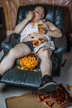 Un adicto a la televisión gordo comiendo una hamburguesa enorme y viendo la televisión. La fuerte iluminación de la televisión ilumina la habitación oscura. Foto de archivo