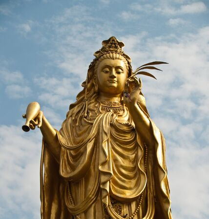 Golden Chinese goddess statue with blue sky Stock Photo