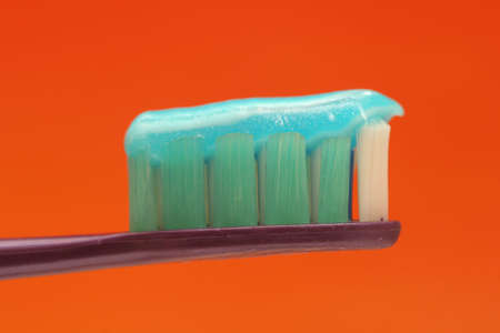 toothcare: Macro of a toothbrush with toothpaste against orange background Stock Photo