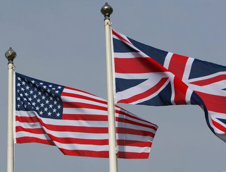 The American Stars and stripes flying from a flagpole next to the Union Jack of Great Britain