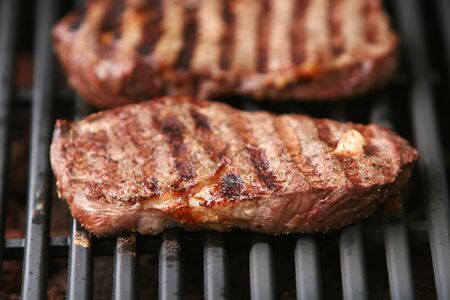 beef steak being grilled on a barbeque grill Stock Photo