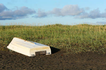 battered land: A single white boat lying upside down on the beach, sand, dunes and clear skies