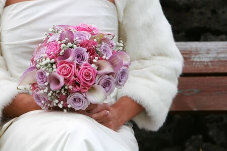 A bride sitting alone with the bridal bouqet in her hands photo
