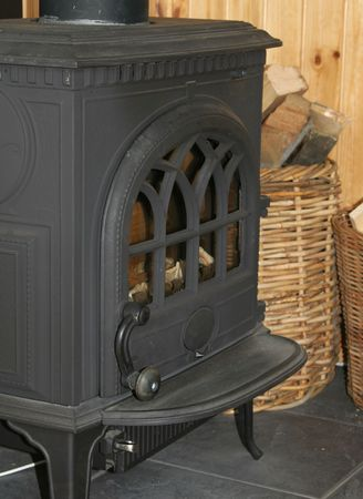 An old black cast iron fireplace with baskets of firewood next to it