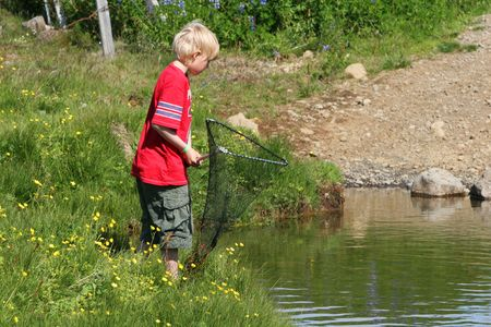 A boy having fun during summer, looking for fish in a small river Stock Photo - 755149