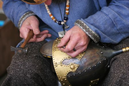 circular muscle: A craftsman making a medieval soldiers helmet the oldfashioned way,