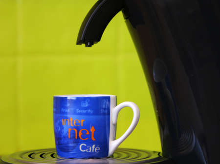 Coffeecup marked with internet and cafe standing on a coffemaker with a bright green background Stock Photo - 755438