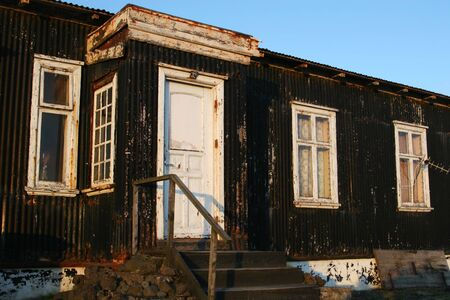 Front of an old condemned house, peeling paint, rust and decay very evident photo